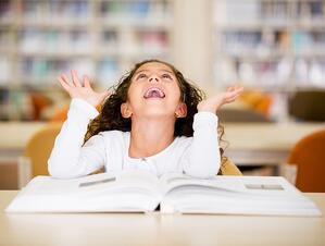 Excited schoolgirl at the library reading a book